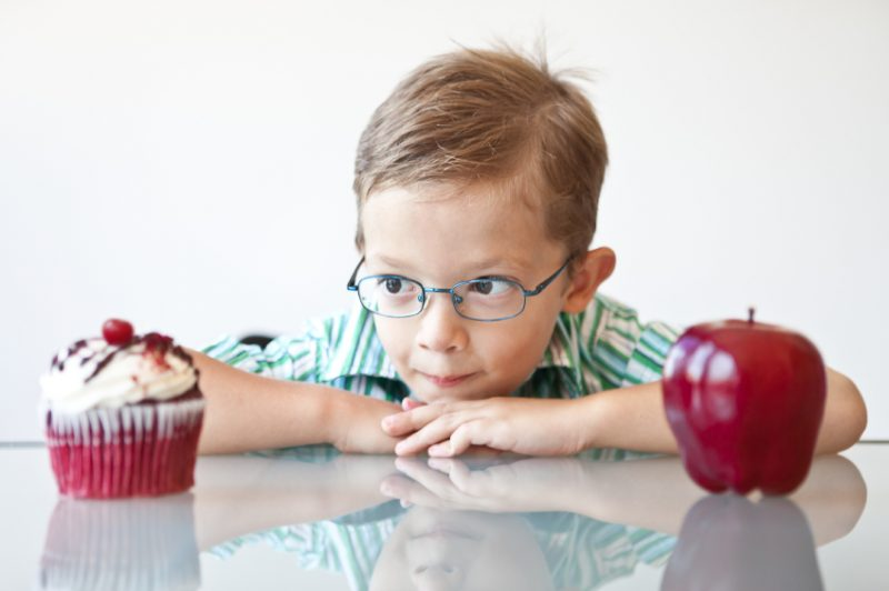 A little boy choosing between a cupcake and apple... Looks like the cupcake is the winner.